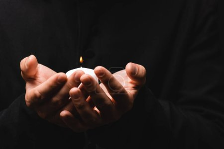 Photo pour Vue partielle du prêtre tenant une bougie allumée isolée sur noir - image libre de droit