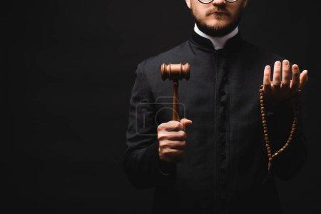 Photo pour Vue recadrée d'un prêtre barbu tenant un marteau en bois et des perles de chapelet isolés sur du noir - image libre de droit