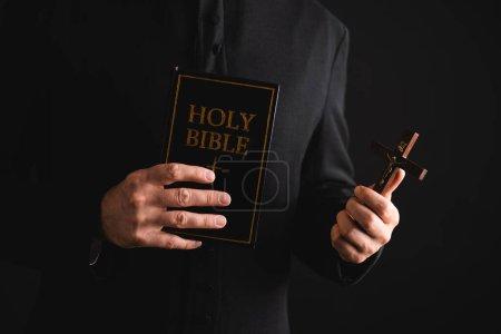 Photo pour Vue recadrée du prêtre tenant la croix et la sainte bible isolée sur noir - image libre de droit