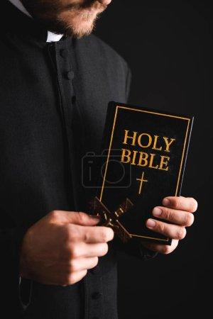 Photo pour Vue recadrée du prêtre barbu tenant la croix et la sainte bible isolée sur noir - image libre de droit