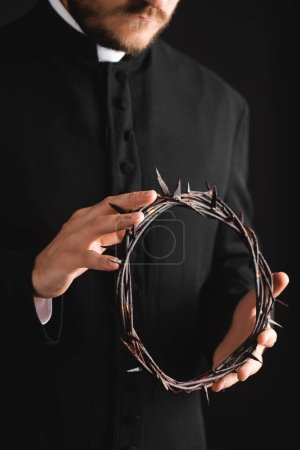 Photo for Cropped view of bearded priest holding sharp wreath with spikes isolated on black - Royalty Free Image