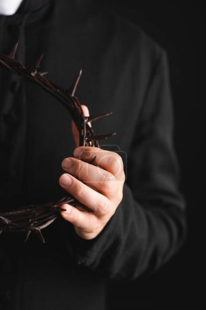 Photo for Selective focus of priest holding sharp wreath with spikes isolated on black - Royalty Free Image