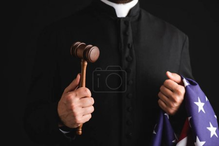 Photo pour Vue recadrée du prêtre tenant un marteau en bois et drapeau américain isolé sur noir - image libre de droit