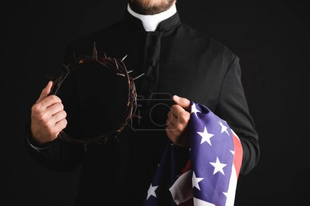 Photo for Cropped view of priest holding wreath with spikes and american flag isolated on black - Royalty Free Image