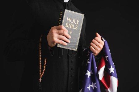 Photo pour Vue recadrée du prêtre tenant la bible sainte, drapeau américain et chapelet perles isolées sur noir - image libre de droit