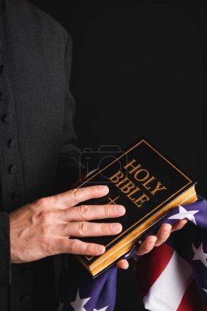 Photo pour Vue recadrée du prêtre tenant la bible sainte et drapeau américain isolé sur noir - image libre de droit