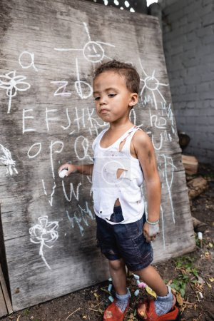 African american child in torn clothes holding chalk near chalkboard