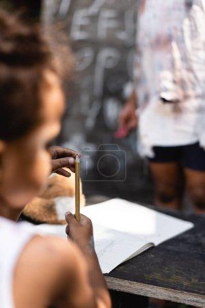 Photo pour Foyer sélectif de pauvre garçon afro-américain tenant crayon près de sœur - image libre de droit