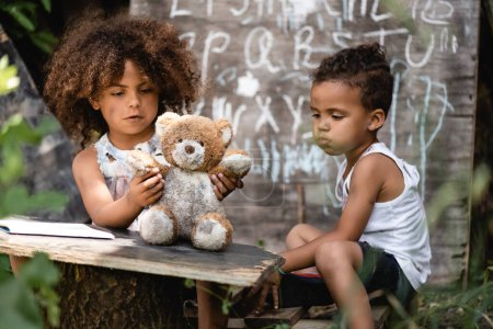 Photo for Selective focus of poor african american kid playing with dirty teddy bear near brother - Royalty Free Image