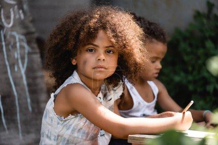 Photo pour Foyer sélectif de l'enfant afro-américain tenant crayon près de frère assis à l'extérieur - image libre de droit