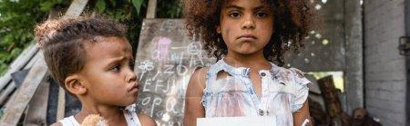 Photo pour Récolte panoramique de triste et pauvre enfant afro-américain près de frère bouleversé à l'extérieur - image libre de droit