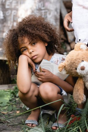 Photo for Upset and poor african american kid holding notebook near child standing with dirty teddy bear - Royalty Free Image