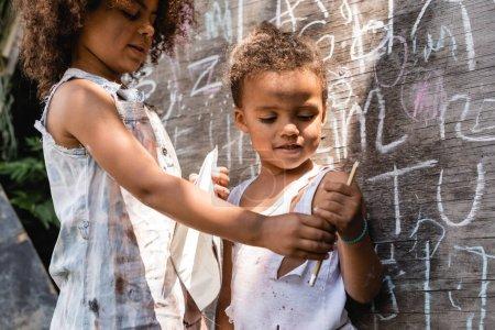 Photo pour Foyer sélectif des enfants afro-américains pauvres en vêtements déchirés debout près du tableau noir et tenant crayon - image libre de droit