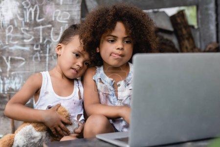 Photo pour Foyer sélectif de pauvre enfant afro-américain sortant la langue près de frère et utilisant un ordinateur portable à l'extérieur - image libre de droit