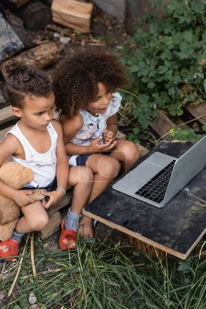Photo pour Vue grand angle des enfants afro-américains pauvres en vêtements déchirés regardant ordinateur portable à l'extérieur - image libre de droit