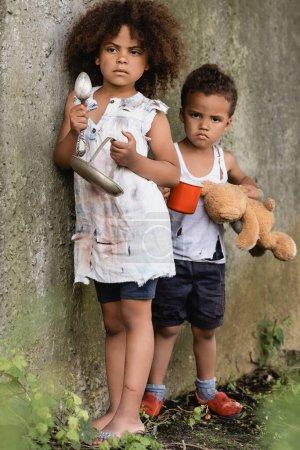 Photo pour Concentration sélective des enfants afro-américains sans abri tenant assiette et tasse tout en mendiant l'aumône dans le bidonville - image libre de droit