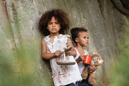 Photo for Selective focus of poor afrian american kid holding metal spoon and plate near brother with cup and dirty teddy bear in slum - Royalty Free Image