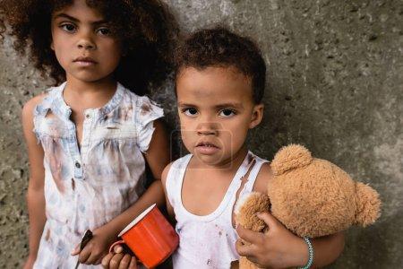 Photo pour Pauvres enfants afro-américains vêtus de vêtements sales avec une tasse en métal et un ours en peluche regardant une caméra près d'un mur en béton à l'extérieur - image libre de droit