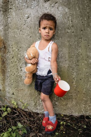 Photo for Dissatisfied african american child in dirty clothes begging alms near concrete wall in slum - Royalty Free Image
