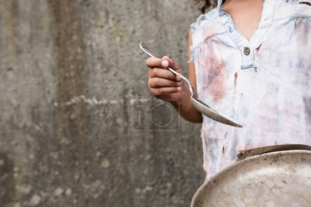 Photo for Cropped view of african american child holding metal plate and dirty spoon on urban street - Royalty Free Image