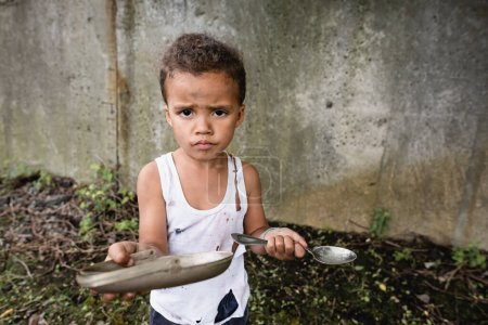 Photo for Dissatisfied african american boy holding dirty plate and spoon and looking at camera on urban street - Royalty Free Image