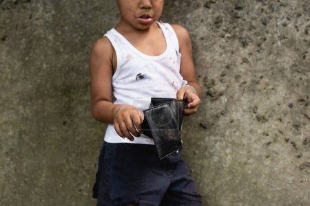 Photo for Cropped view of poor african american child in messy clothes holding wallet on urban street - Royalty Free Image