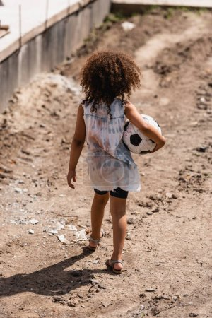 Back view of poor african american child holding soccer ball on dirty road of slum
