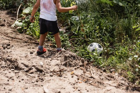 Cropped view of destitute african american boy standing near soccer ball in grass near dirty road on urban street