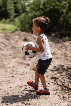 Photo for Side view of destitute african american boy holding soccer ball on dirty road in slum - Royalty Free Image