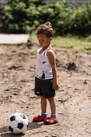 Photo for Poor african american boy in messy clothes standing near football on ground on urban street - Royalty Free Image