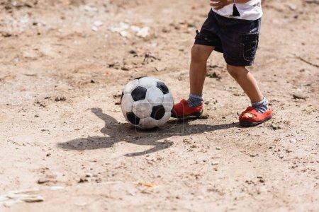 Foto de Vista recortada del pobre chico afroamericano jugando con pelota de fútbol en camino sucio en la calle urbana - Imagen libre de derechos