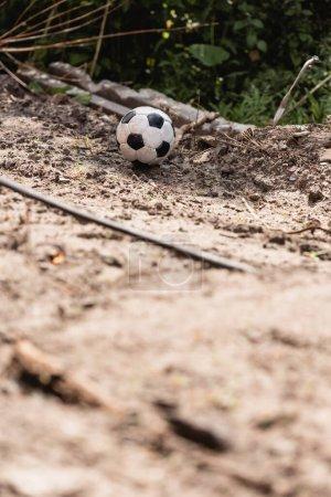 Photo pour Concentration sélective du ballon de football sur le terrain de la route sale sur la rue urbaine - image libre de droit