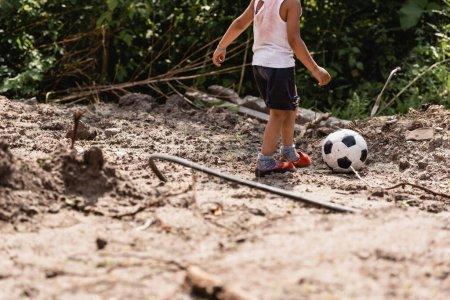 Photo pour Vue recadrée d'un enfant afro-américain démuni jouant au football sur une route sale dans un bidonville - image libre de droit