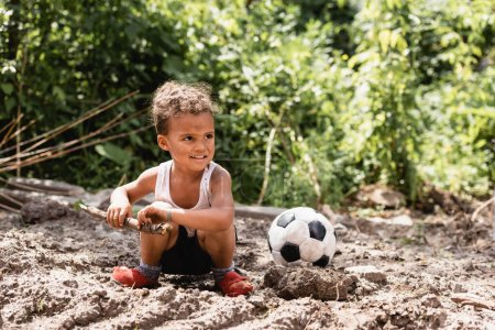 Photo for Smiling african american child with messy face holding wooden twig near football on dirty road in slum - Royalty Free Image