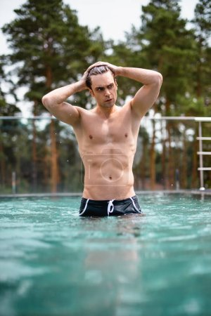 selective focus of muscular man touching wet hair and looking away in swimming pool