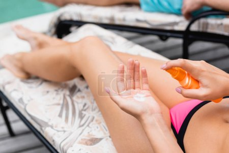 Photo for Cropped view of woman applying sunscreen on hand - Royalty Free Image