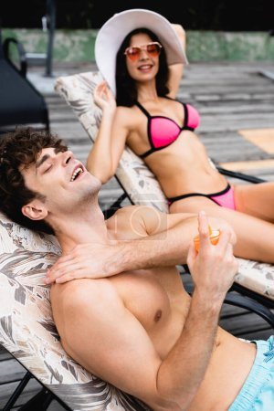 Photo for Selective focus of shirtless man applying sunscreen near happy girl in straw hat and sunglasses - Royalty Free Image