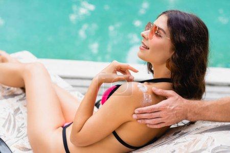 man applying sunscreen on cheerful girlfriend near swimming pool