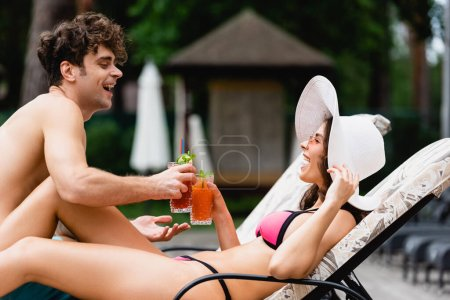 cheerful couple smiling while clinking alcohol cocktails