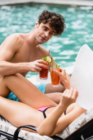 Photo pour Homme heureux tenant cocktail tout en cliquetis avec fille en chapeau de paille - image libre de droit