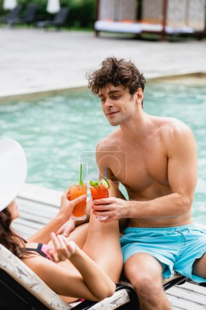 muscular man holding cocktail while clinking with girl in straw hat