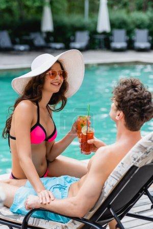 Photo pour Femme heureuse en lunettes de soleil et chapeau de paille tenant cocktail et cliquetis avec l'homme près de la piscine - image libre de droit