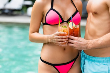 cropped view of couple in swimwear holding glasses with cocktails
