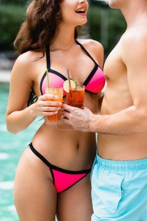 vista recortada de pareja feliz en traje de baño sosteniendo vasos con cócteles