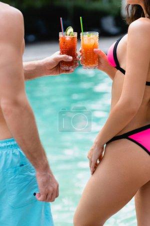 Photo pour Vue recadrée de l'homme et de la femme en maillot de bain tenant des lunettes avec des cocktails - image libre de droit