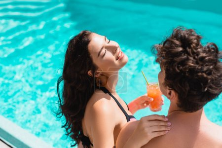 Photo for High angle view of happy woman with closed eyes touching man and holding cocktail near swimming pool - Royalty Free Image