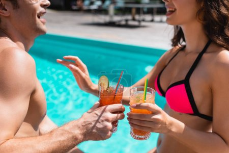 Photo for Cropped view of happy man and woman holding cocktails near swimming pool - Royalty Free Image