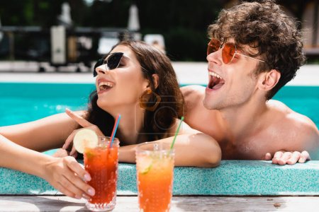 happy woman in sunglasses pointing with finger near man and cocktails