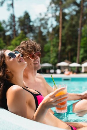 cheerful young woman in sunglasses holding cocktail near man in swimming pool