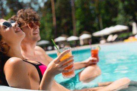 Photo pour Foyer sélectif de fille gaie dans les lunettes de soleil tenant cocktail près de l'homme dans la piscine - image libre de droit
